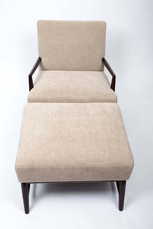 Newly upholstered armchair with ottoman by T. H. Robsjohn-Gibbings.