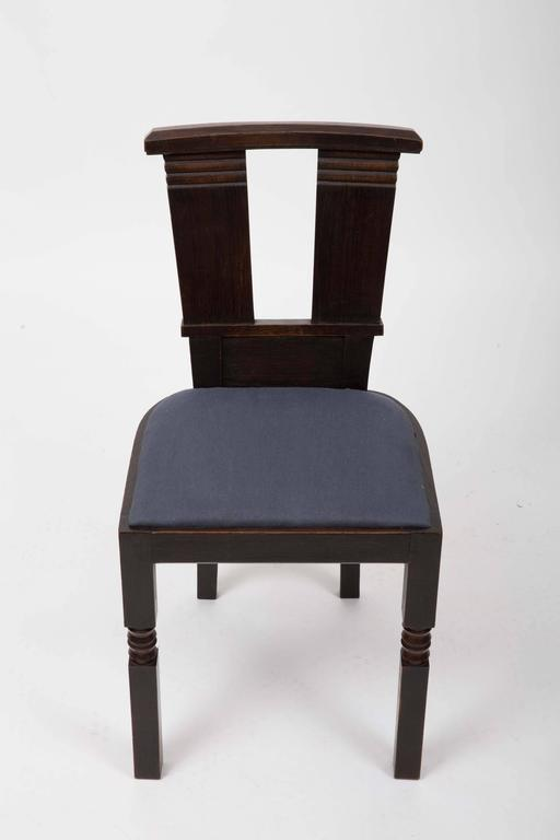 Dark brown oak dining chairs with navy linen cushions, newly upholstered.