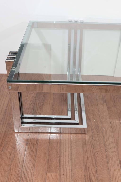 Two-tier chrome coffee table with Lucite legs and glass tops.
