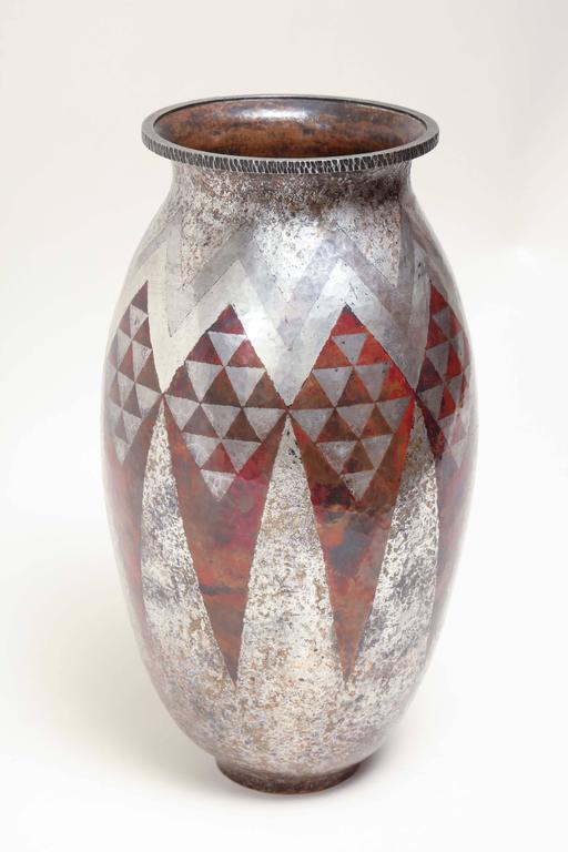 Copper and silver ovoid vase with a geometric design of triangles in red and silver.