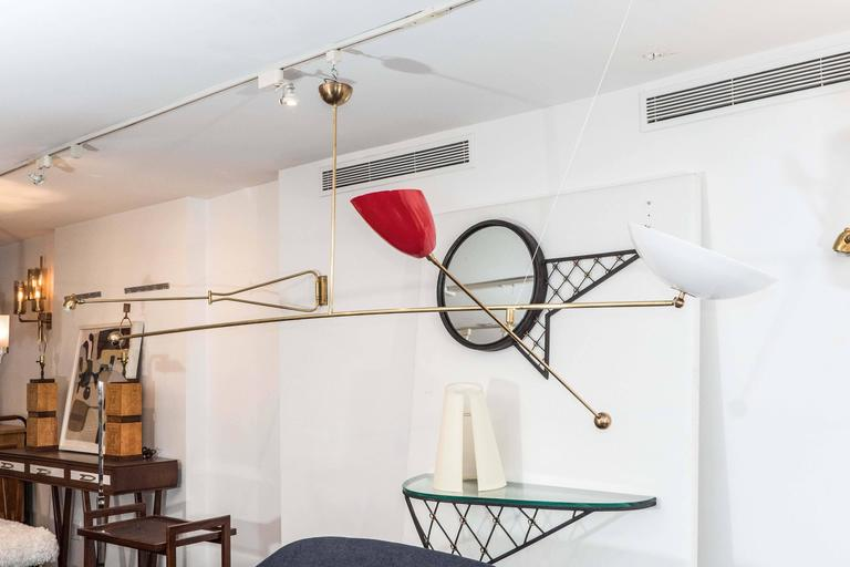 Counter balance chandelier in the style of Angelo Lelli with double articulated brass shades. The shades are powder coated in red and white. The large white shade measure 13.5