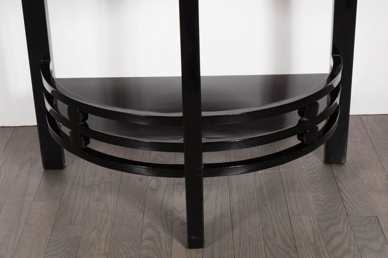 An Art Deco streamline Machine Age two-tier demilune end table/side table in black lacquer with vitrolite top. This Art Deco demilune table in all black lacquer features a base with a triple row of lines separated by a circular detail, the back of