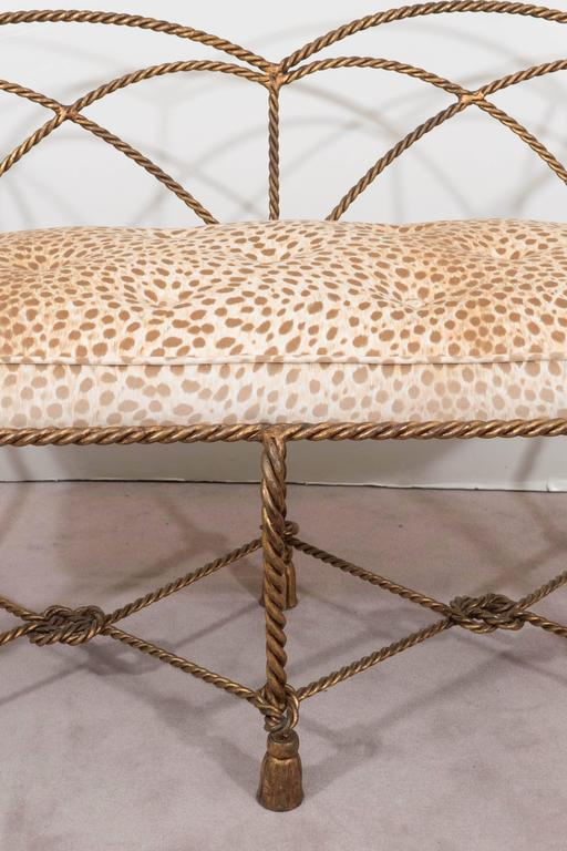 This vintage Italian settee, produced circa 1950s, comes in a gold gilt iron frame, designed as twisted rope with tassels, with cushioned seat, upholstered in leopard print velvet. The settee remains in very good condition, consistent with age; seat