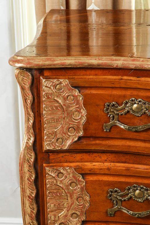 18th century Lyonaise three drawer walnut commode with carved giltwood detail and bronze drawer pulls. Both sides of this piece have two panelled side profiles. From the connoisseur collection in Los Angeles, California.