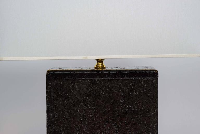 Original and unusual pair of lamps made of polished and painted lava rock, with brass setting.