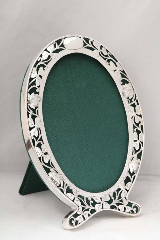 Art Nouveau, sterling silver, pierced, footed oval picture frame, George A. Henckel & Co., New York, circa 1905. Frame is pierced so that green velvet shows through. Flowers are slightly