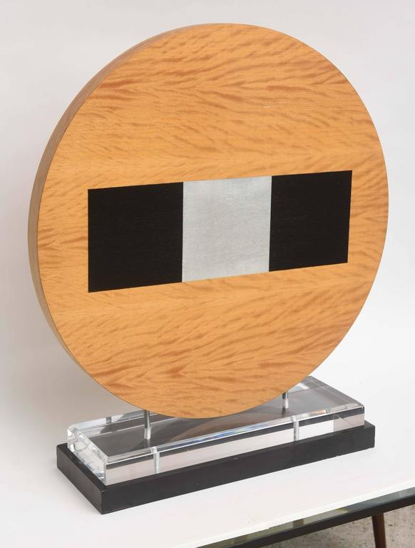 The circular wood with ebonized and silver leaf area on marble and acrylic stand