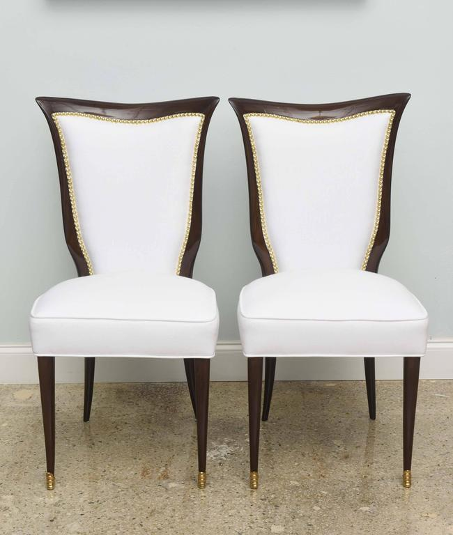 The curved and scrolling back with upholstery and nail heads above splayed legs with fine brass sabots.
