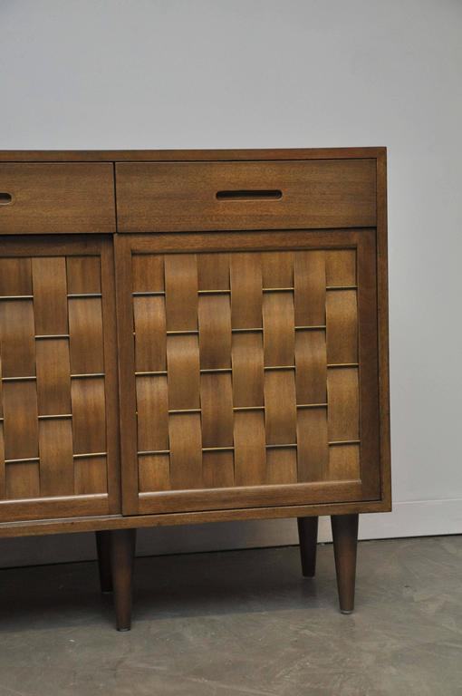 Large four-door sideboard designed by Edward Wormley for Dunbar. Model #5668. Original walnut finish on mahogany. Brass details on doors. Four sliding doors.