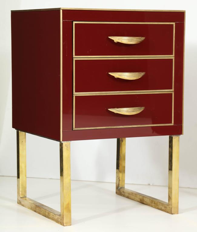 This pair of Italian Mid-Century nighstands is absolutely exquisite. Made of wood and covered in a high-gloss burgundy or deep red colored Venetian opaline glass with beautiful polished brass inlays, pulls and brass flat legs. 