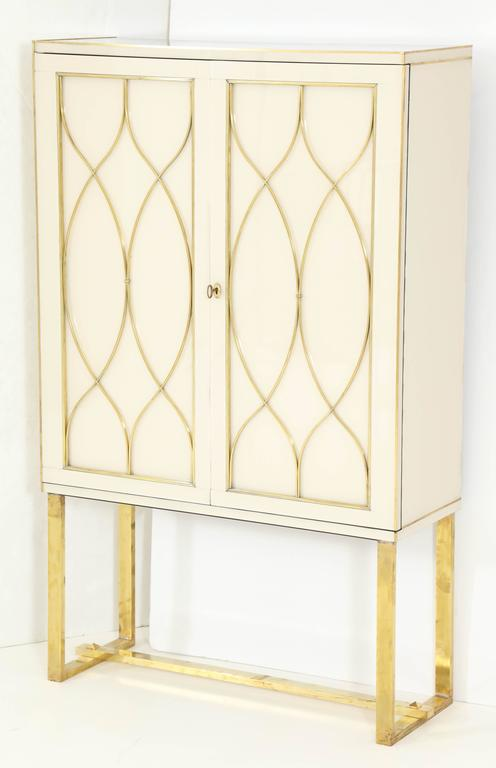 This Italian Mid-Century tall cabinet or dry bar is absolutely exquisite in its detail and craftmanship. Made of wood and covered in a high-gloss ivory colored venetian Opaline glass with beautiful brass inlays and brass flat front legs. Working