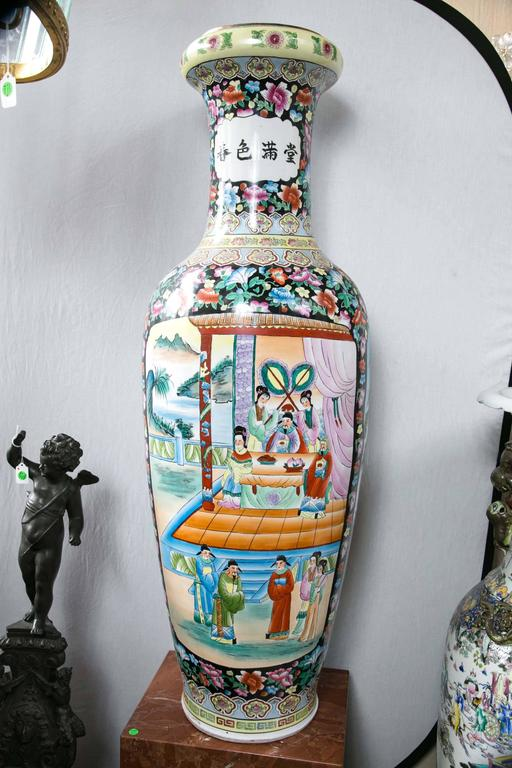 This pair have a Famille noire ground decorated with floral motifs. Each has two panels of painted figures in court settings. Chinese calligraphy decorates the necks.