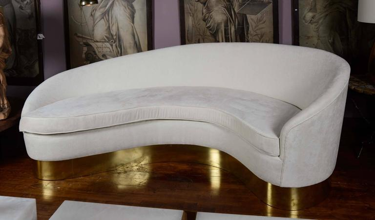 Curved sofa upholstered with ecru fabric, cushions, brass base.