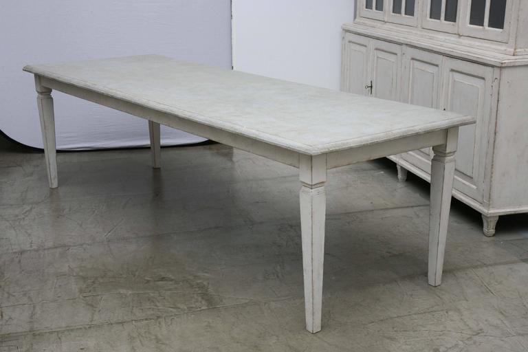 Antique long Swedish Painted dining farm table with a beautiful patina. The table top in a painted distressed gray color with a carved ogee edge and the bottom in light Gustavian white-gray painted distressed finish,  square tapered simple