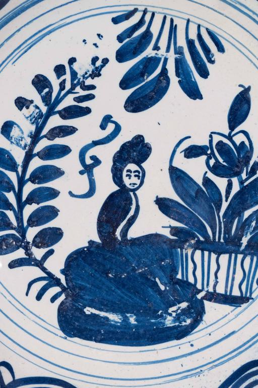 An 18th century Dutch Delft charger painted in cobalt blue with a scene showing a lady seated in a  garden. The border is decorated with linked concentric circles. It is the naive aspect of this charger which makes it special.  Dimensions: diameter