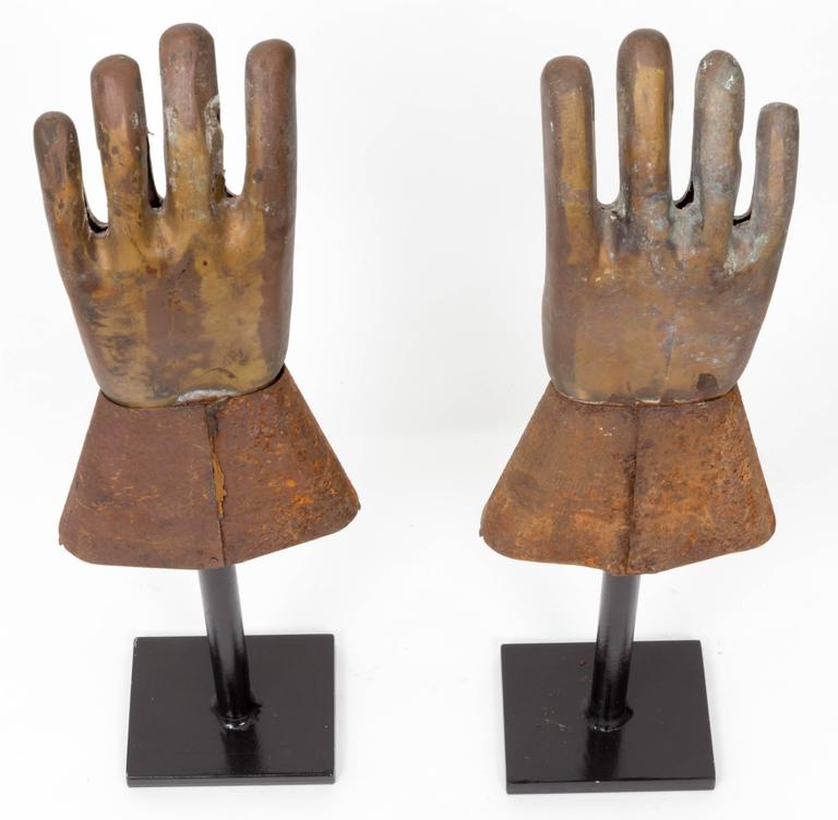 Rare pair of metal glove molds on custom black iron stands.