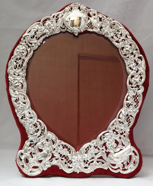 Large, sterling silver, heart-form picture frame, Dominick & Haff, New York, circa 1895. Pierced work allows burgundy velvet to show through the design. Edges of heart-shaped glass are beveled. Measures: 14 1/4