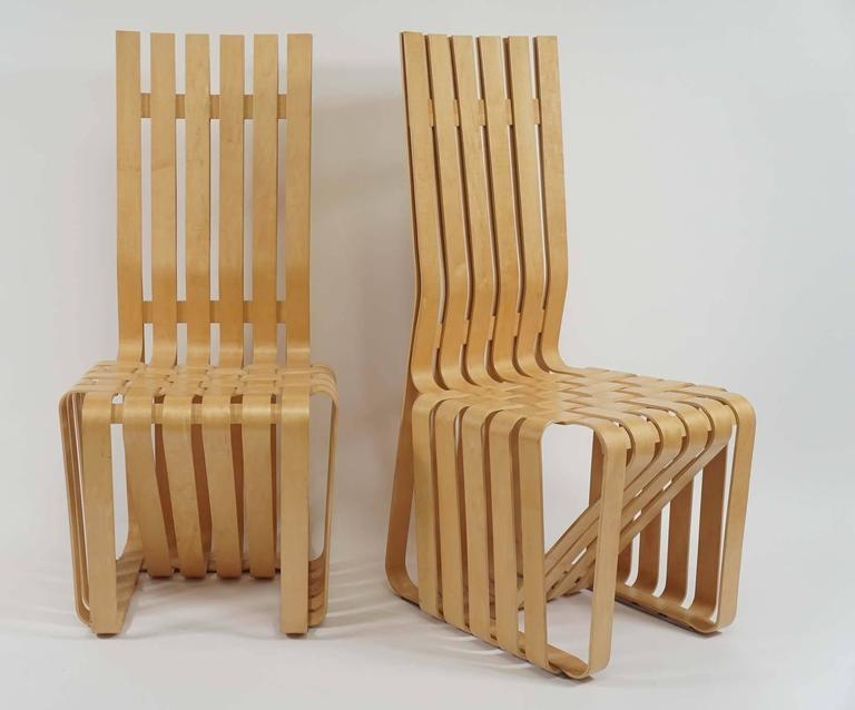 A wonderful pair of sculptural chairs by Frank Gehry. Inspired by the strength of apple crates, he created these woven bent maple chairs. They retain the Knoll and Gehry signature along with the date they were made. One is missing the plexi glide on