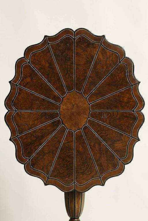 Unusual 19th century Swedish tilt-top table with scalloped top having faux painted marquetry top, over octagonally shaped shaft, standing on scrolled legs, the whole painted in simulated walnut, ivory and salamander and having graphic form.
