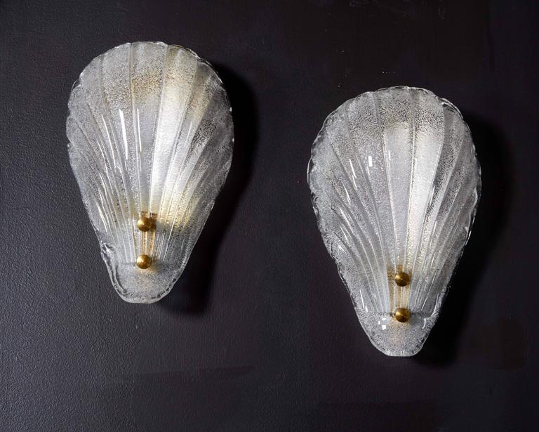 Elegant wall lights featuring stylized sea shell design in handblown Murano glass. Shades have fluted details and textural bubble technique. The hidden frame is finished in a polished brass with matching stud fittings, and has been newly rewired to