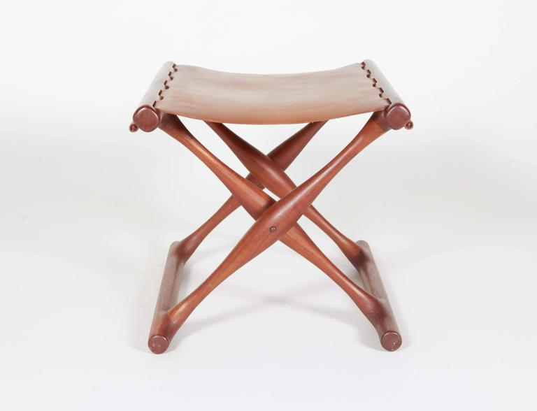 This sculptural folding stool is brilliantly constructed with wooden pins securing the original leather seat.