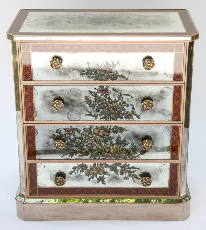 Pair of commodes, with all surfaces covered in reverse painted mirror plate, each having a rectangular top with canted corners, framed in dark red and gilt, crosshatched border, over bevelled apron, on four stacked drawers, hand-painted decoration