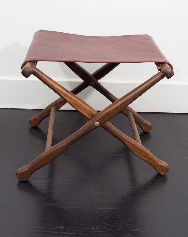 Pair of folding stools in walnut and leather, sling freshly replaced.