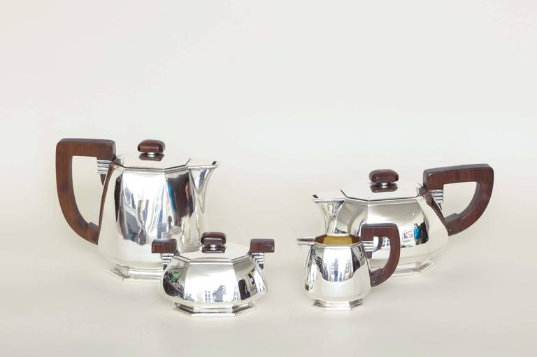 """With wide cut-off corners and handles and finials in Brazilian rosewood. Measures: Coffee pot- 4 3/4"""" high; 9"""" wide; 4 5/8"""" deep. Teapot-6 3/8"""" high; 7 3/4"""" wide; 4 ¼"""" deep. Sugar-3 ½"""" high; 5 ½"""" wide; 4' deep. Creamer-3 ¾"""" high; 4 ¾"""" wide; 2"""