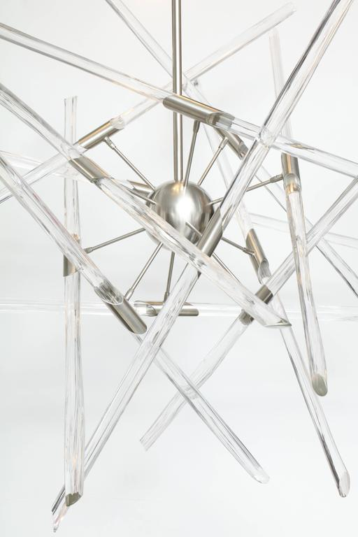 Contemporary American artist Barry Entner's Tangent Chandelier is comprised of clear textured solid glass sticks and a nickel plated steel frame. The canopy holds 5 LED round lights that shine down on the adjustable sticks as they orbit a 5