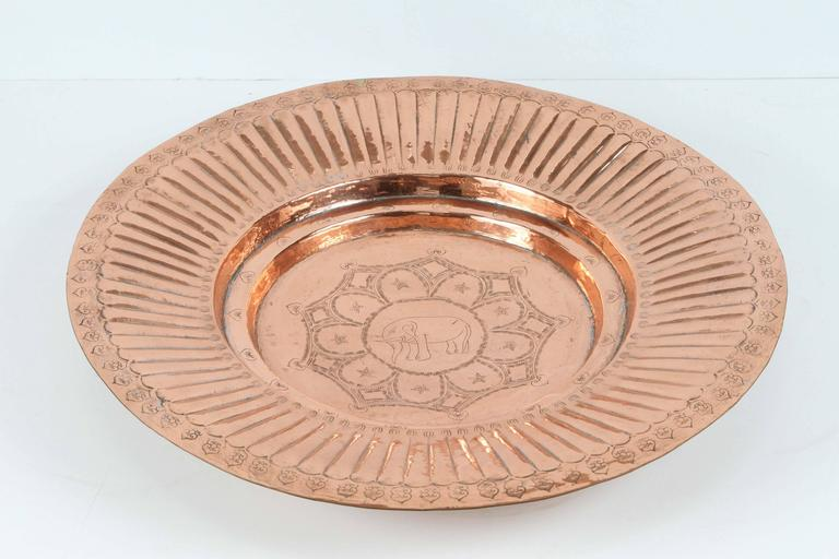 Polished round Asian Rajasthani metal copper tray, hand-hammered with geometric design in the middle, and an elephant in the center, the elephant in the Asian culture means protection and long life. Handcrafted in India, Rajasthan. Great to use as a