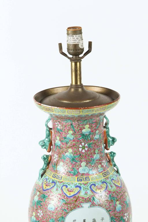 Chinese ceramic vase turned into a table lamp. Figural scene, Chinese script and nice pink and turquoise foliage designs. Wooden Chinese style base.