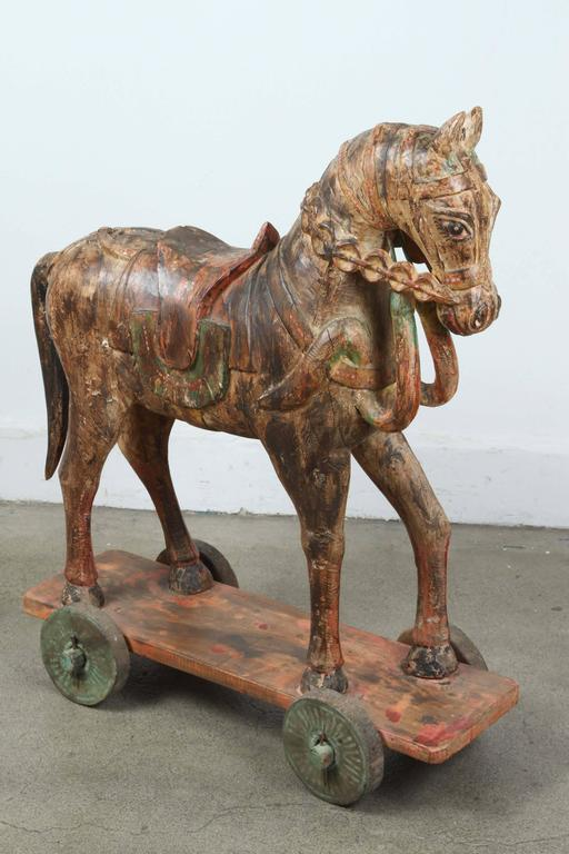 Pair of 19th century hand-carved oversized wooden Indian temple horses with poly-chrome decorated sitting a top of a wheeled board. The two horses are almost the same size, but different designs, carving and colors, they are not matching. Very nice