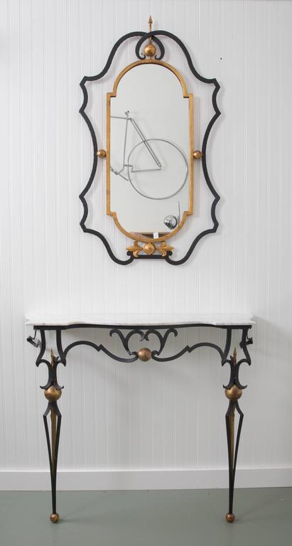Hand-wrought iron with gold accents wonderful scroll work on tapered legs ending in ball feet. Marble-top mirror: 41
