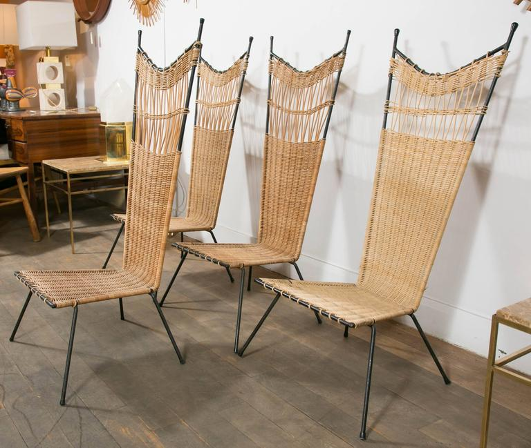 A elegant set of four slipper chairs,  black lacquered metal structure and woven wicker by Raoul Guys, France, circa 1950.  These chairs can be sold by pair.
