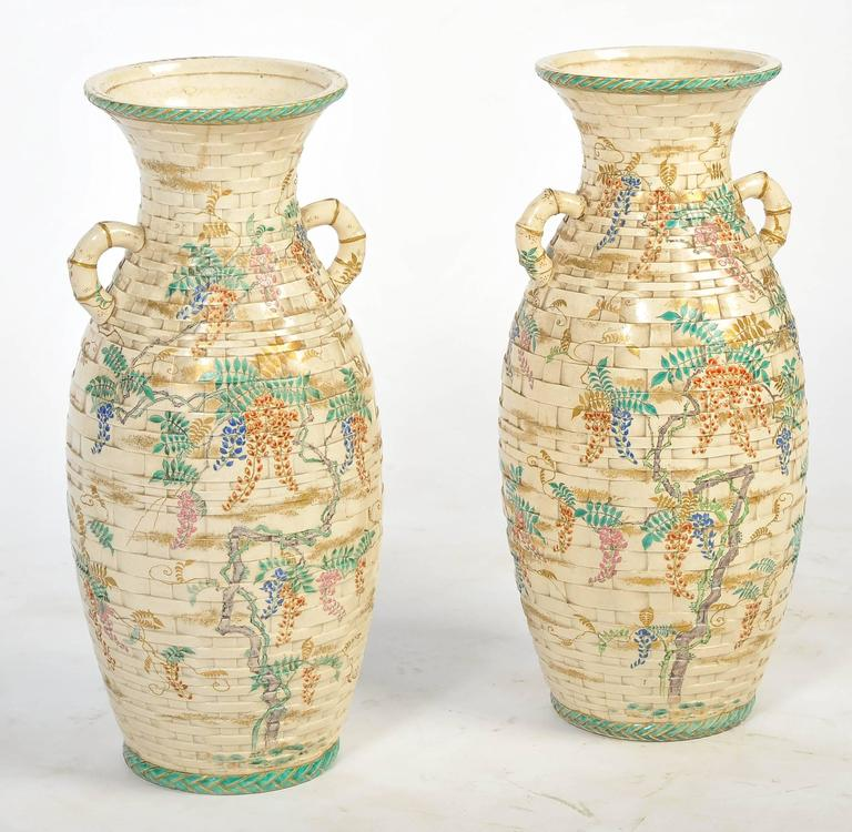A very decorative pair of Japanese Satsuma vases, having a faux basket weave pattern with bamboo like handles and foliate painted decoration. We can arrange of this pair of vases to be lamped if needs be, within the price.
