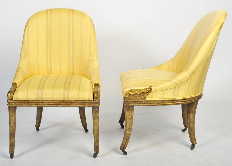 A very stylish pair of cream painted Regency slipper side chairs, having stuff over upholstery, carved scrolls to either side and raised on out swept sabre legs, terminating in brass castors.