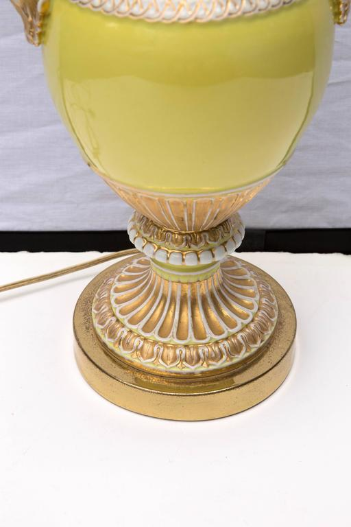 This 19th century vase have a beautiful yellow color with gilt gold highlights and curled white snakes as handles. To become a table lamp the vase has been capped and set on a base.