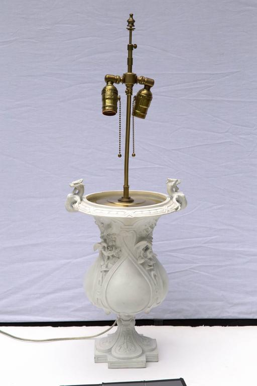 A decorative bisque porcelain urn marked by Jean Gille of Paris, France with a raised blue J over G, dating from 1840-1868. Now converted to a two socket table lamp with brass hardware. Measurements are the urn itself.