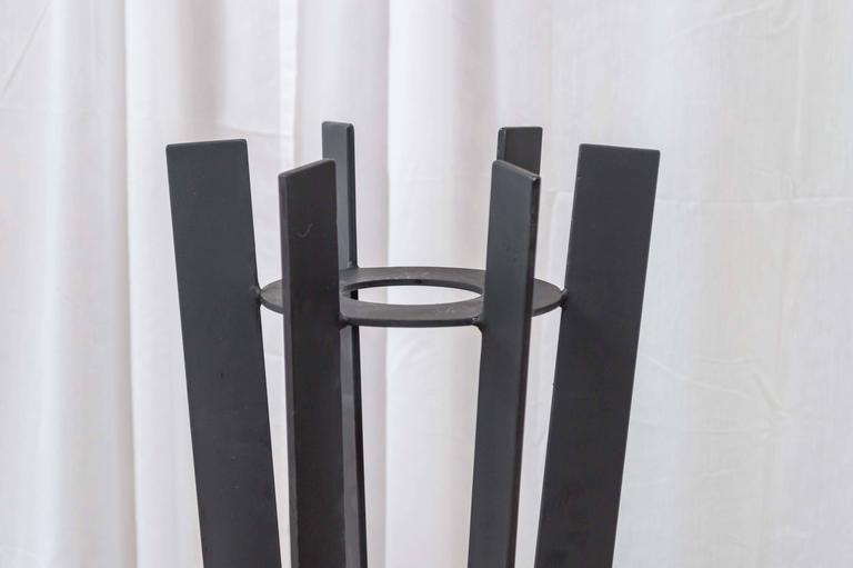 A pair of tall wrought iron plant stands that are as sculptural as they are functional.  The body and base are each comprised of six 2 in deep, matte black fins. They support a 7.50 in circular shelf with a 3.50 in opening in its center, on or in