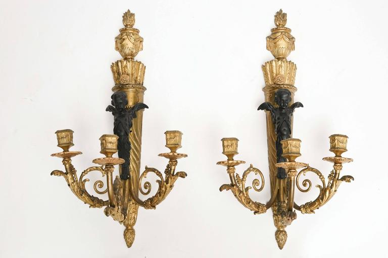 The sconces are fashioned with patinated cherubs.