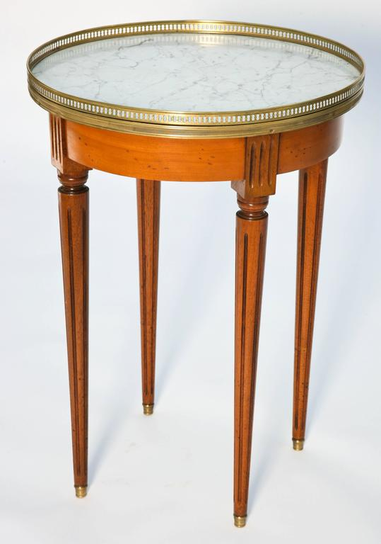 Bouillotte table, having round veined white marble top, surrounded by a pierced gallery of brass, raised on fluted tapering round legs.  Stock ID: D9321