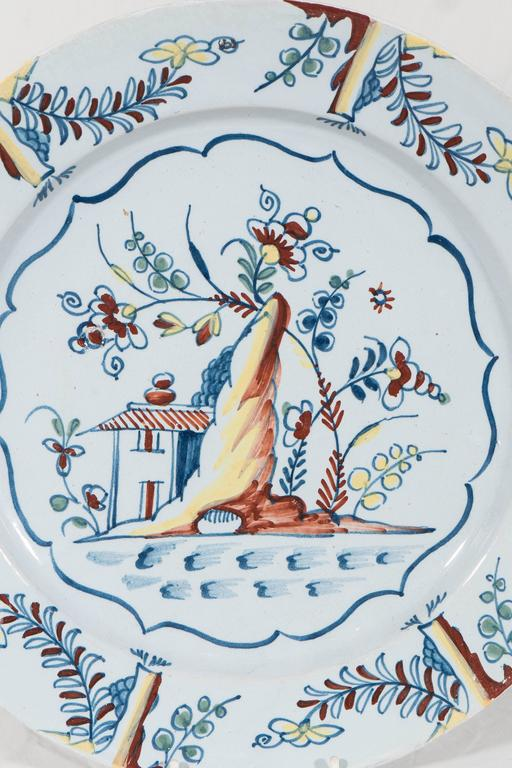 A lovely mid-18th century Bristol Delft charger with the well painted vibrant scene. We see a traditional country home, a flowering tree, and a rocky outcropping. The scene features  the polychrome colors in use at Bristol: yellow, iron red, cobalt