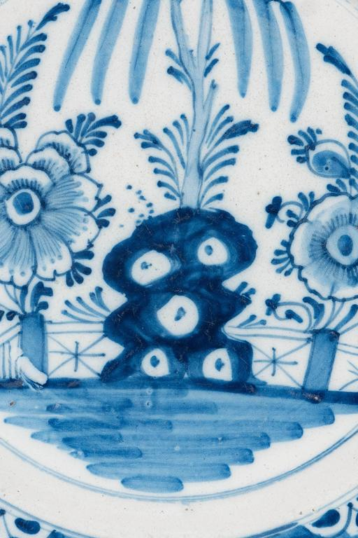 We are pleased to offer this pair of Blue and White Delft chargers hand=painted with a naive garden scene. The oversize flowers and the taihu rock are seen in front of the garden fence. The cobalt blue border is decorated with flower heads painted