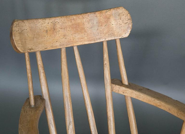 19th century English Folk Art stick chair made out of elm. Surprisingly comfortable and worn on the ends of the arms where someone would have handled to raise themselves from a sitting position. Seat height is 15.5 inches.