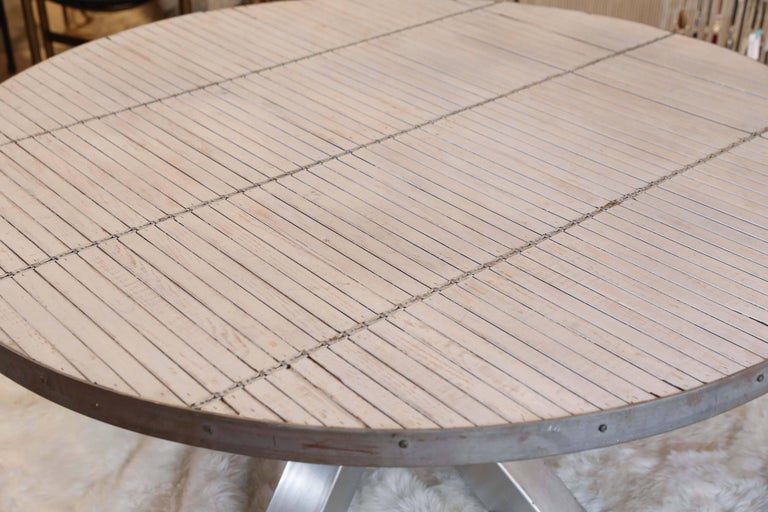 This table was crafted from repurposed materials and features a fantastic steel-clad base and a very unique top made with white washed vintage venetian wood blinds. The finish of the top is somewhat distressed, so please review the images closely.