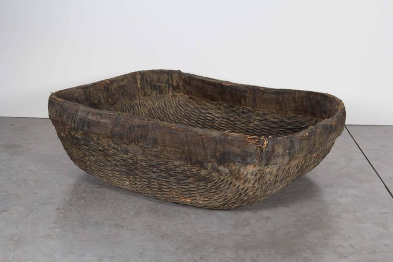 An unusual, large woven willow basket with fabric trim at the top displaying its many years of age in its beautifully worn and faded finish. From Shanxi province, circa 1900. B445.