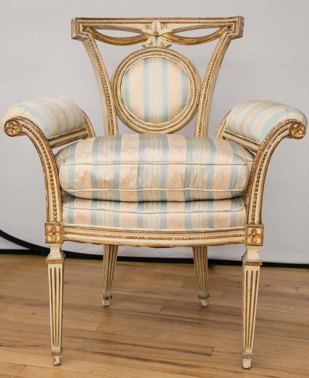 A pair of painted and gilded wood medallion back chairs. Delicate bead and swag detail surround a central flower. Padded scroll form arms sit atop tapering fluted legs.