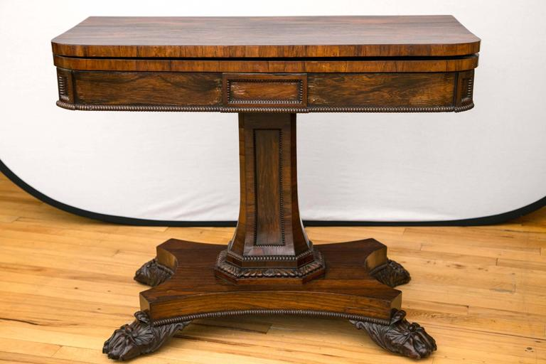 A pair of English rosewood game card tables. The curved front corners include both the folding top and the apron to make a seamless band. The table top is made to fold open and slide or swivel before resting flat. When the game table top is
