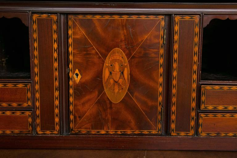 A cylinder desk in the Hepplewhite style, executed in flame mahogany veneers and tulip poplar and yellow pine geometric inlay. The center door is inlaid with a heraldic eagle. Invented in the first half of the 18th century, cylinder desks feature a