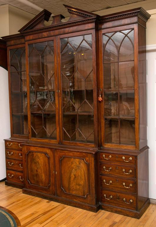 A pair of circa 1760, George III mahogany breakfront bookcases topped by moulded dentil cornices with triangular broken pediment and central rectangular pedestal. Each has two honeycomb mullioned glazed doors in the center, flanked by Gothic arch